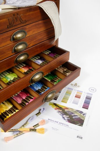Vintage-style wooden chest of drawers containing the 500 colours of DMC stranded cotton